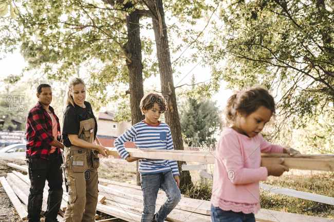 Parents and children carrying wooden plank in backyard