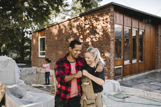 Smiling couple bumping fist while standing against house