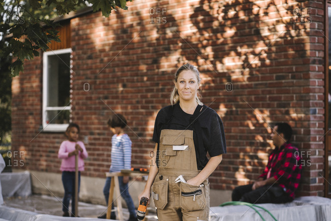Portrait of confident woman with drill machine while family in background against brick wall