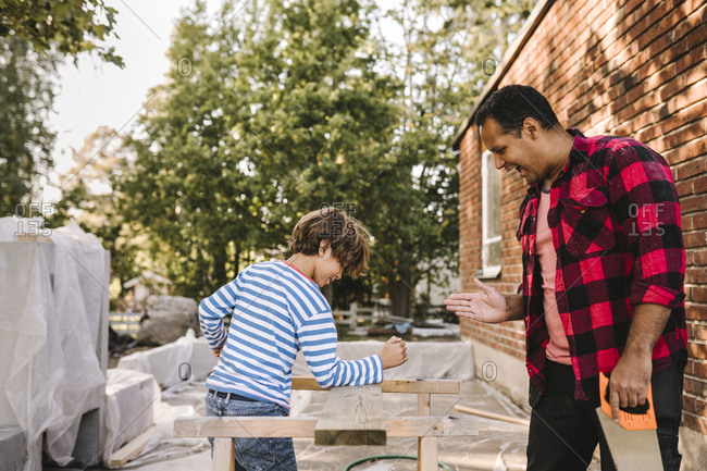 Son breaking wooden plank with hand while smiling father gesturing outside house