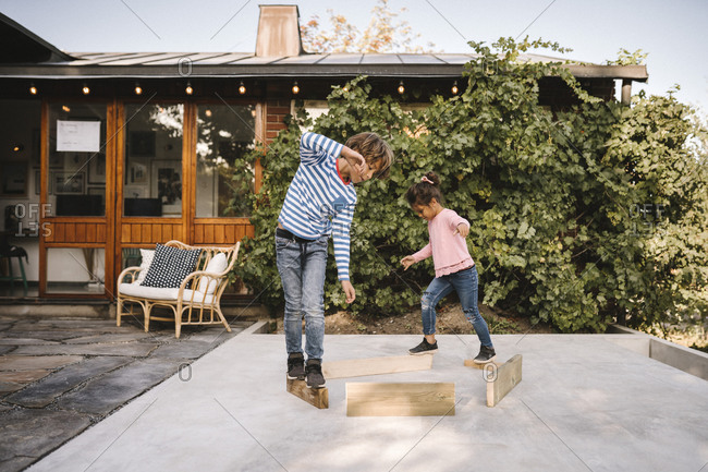 Playful siblings balancing on wooden planks against house