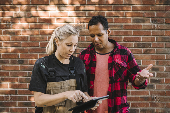 Woman using digital tablet while male partner gesturing against brick wall