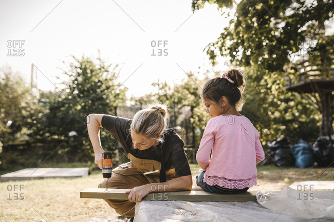 Daughter looking at mother using drill machine on wooden plank in backyard