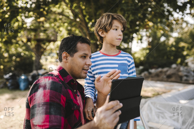 Father with digital tablet gesturing by son in yard
