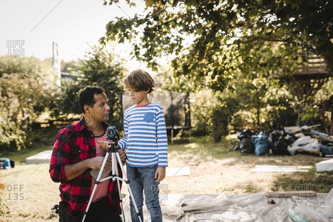 Father teaching surveyor to son in backyard