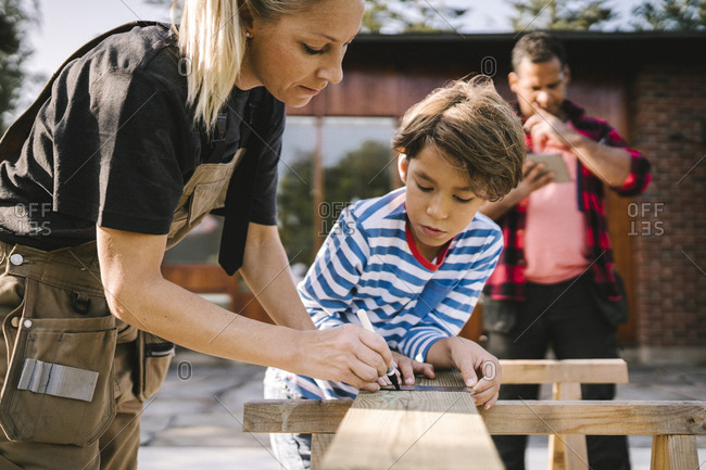 Mother measuring wooden plank by son outside house