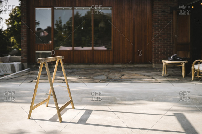 Wooden work table on concrete land against house