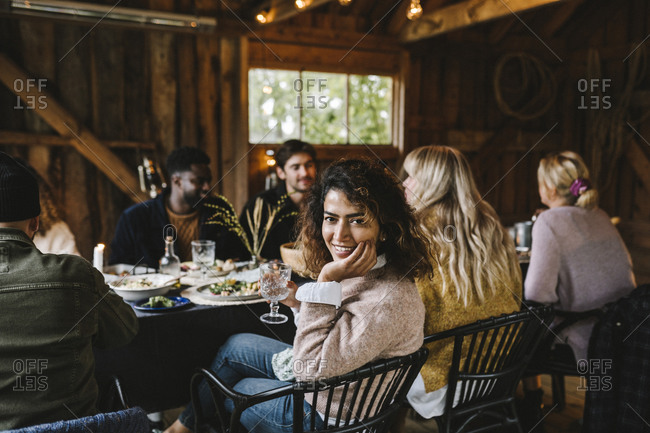 Portrait of smiling woman with hand on chin enjoying by friends during social gathering