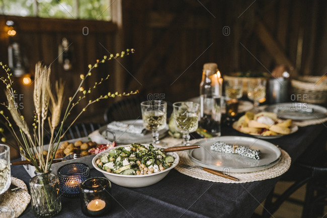 Food in bowl by plate and drinking glass arranged on dining table during social gathering
