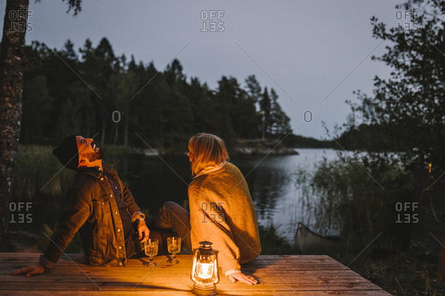 Cheerful male with female partner sitting on pier by lake during sunset