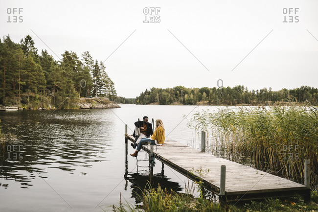 Male and female partners sitting on pier over lake during social gathering