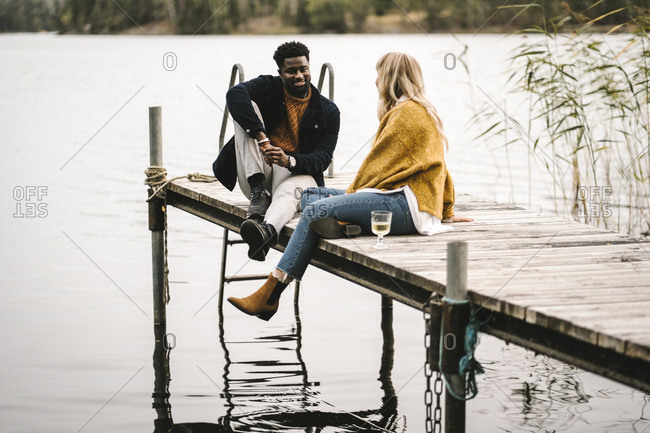 Smiling male and female partners talking while sitting on pier over lake during social gathering