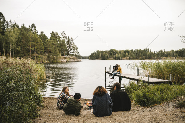 Rear view of male and female talking friends while couple sitting on pier during social gathering