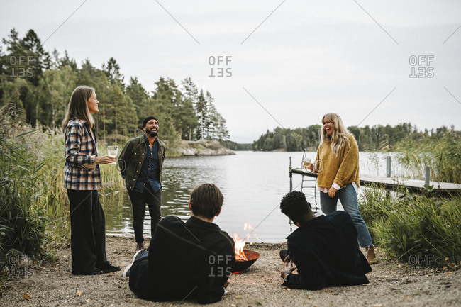Male and female friends enjoying by fire pit near lake during weekend