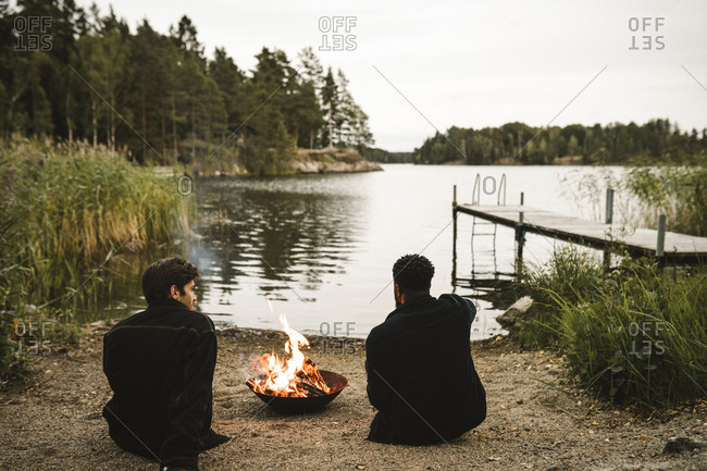 Rear view of male friends talking by fire pit against lake
