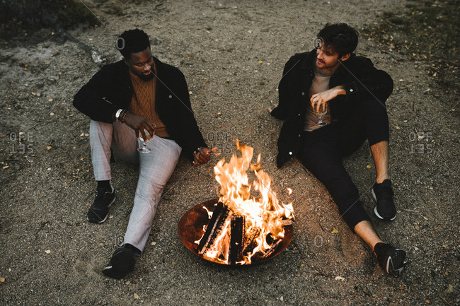 High angle view of male friends talking while sitting by fire pit during weekend