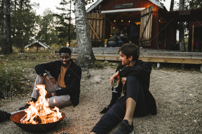 Male friends with drinking glass talking while sitting by fire pit during weekend