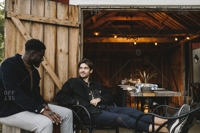 Smiling male friends talking outside cottage during social gathering