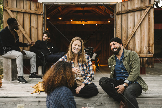 Smiling male and female friends talking while sitting on staircase against cottage during social gathering