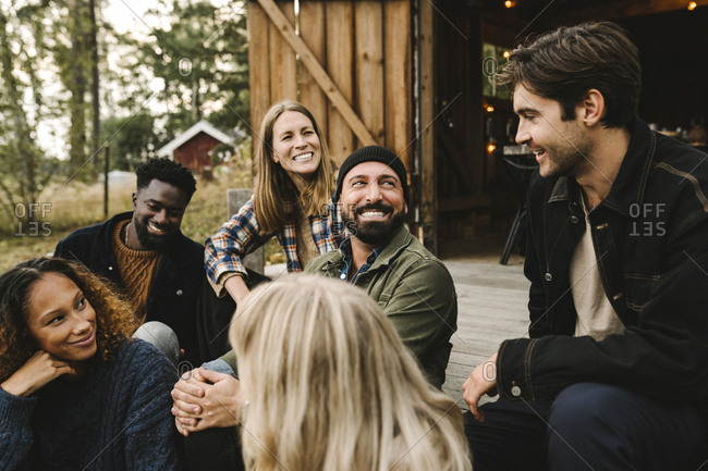 Smiling male talking to friends while sitting outside cottage during social gathering