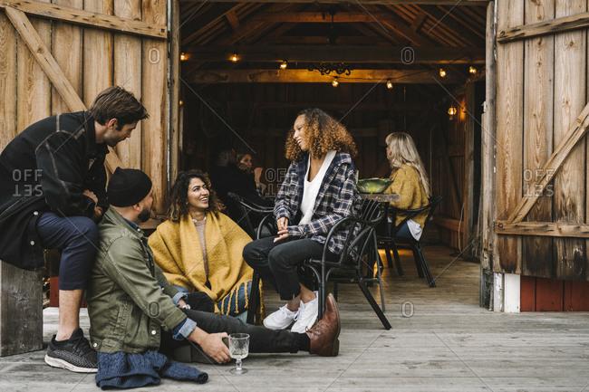 Smiling men and women enjoying while sitting by cottage doorway during social gathering