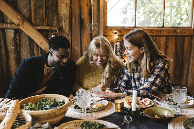 Smiling woman showing smart phone to friends while sitting by dining table during social gathering