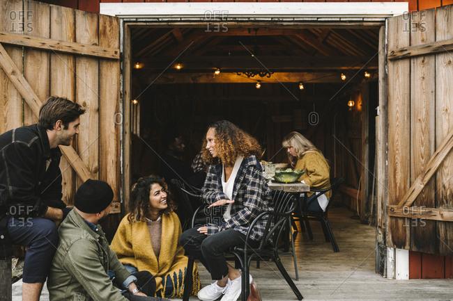 Smiling men and women talking while sitting by cottage doorway during social gathering