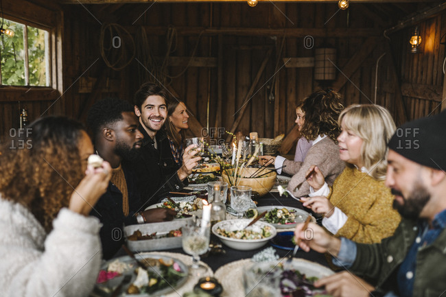 Portrait of smiling man enjoying with male and female friends during social gathering