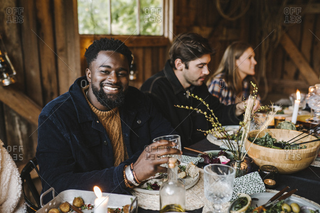 Portrait of smiling man enjoying with female and male friends during social gathering