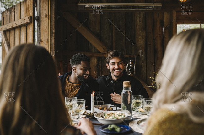 Smiling men talking to female friend by dining table during dinner party