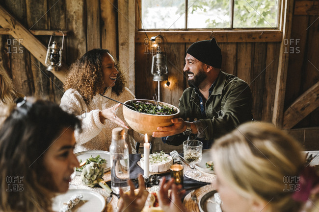 Smiling male giving food bowl to female friend during social gathering