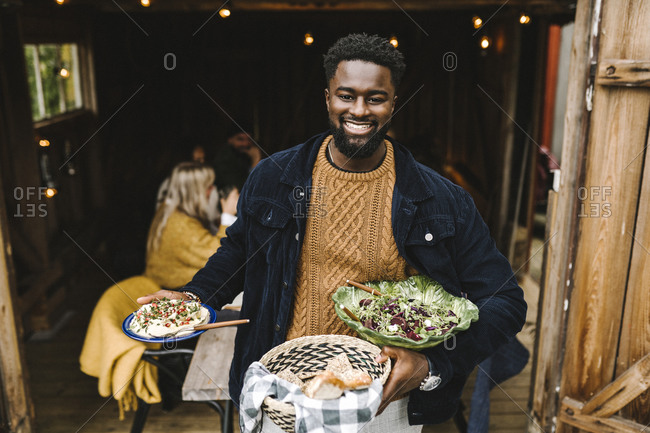 Portrait of smiling man with food standing at doorway during party