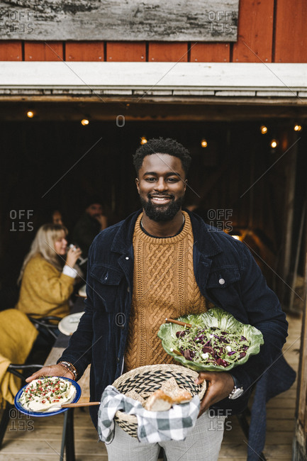 Portrait of smiling man with food standing at doorway during social gathering