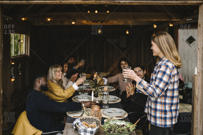 Smiling woman toasting drink with male and female friends while standing by dining table party