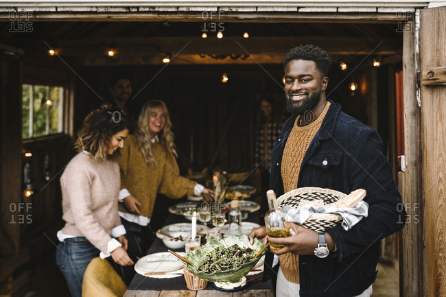 Portrait of smiling man holding food bowl with drink while friends arranging dining table during party