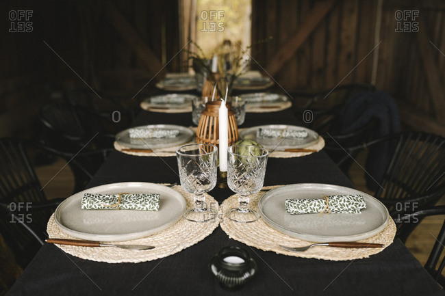 Plates and glasses arranged on dining table for dinner party