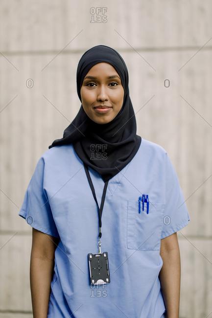 Portrait of smiling female nurse wearing hijab against wall in hospital