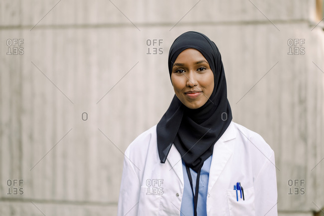 Portrait of smiling nurse wearing hijab while standing against wall in hospital