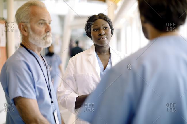 Senior nurse by female colleague talking to coworker in hospital corridor