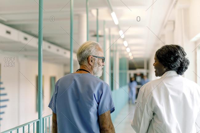 Rear view of senior nurse by female colleague walking in hospital corridor