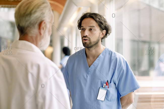 Contemplating nurse talking to senior expert in hospital