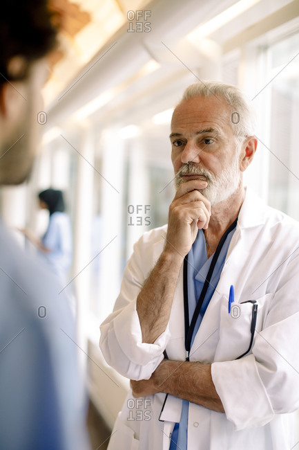 Male nurse talking to contemplating wrinkled expert in hospital