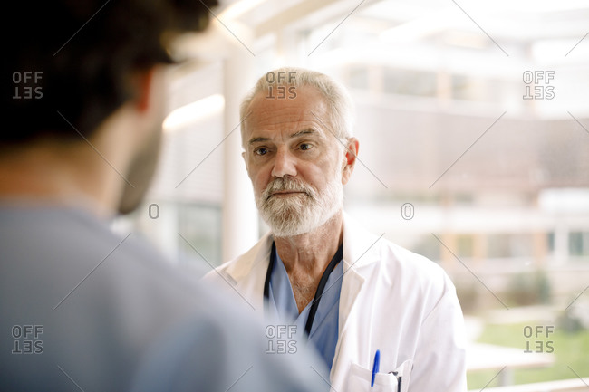 Contemplating wrinkled nurse talking to male colleague in hospital