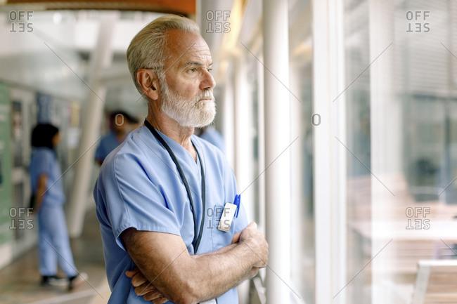 Contemplating senior nurse with arms crossed looking through window in hospital corridor