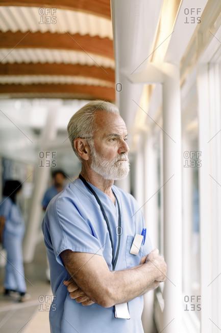 Contemplating senior nurse looking through window in hospital corridor