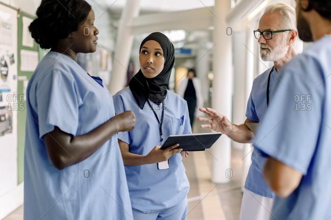 Confident senior male and female nurses talking in hospital corridor