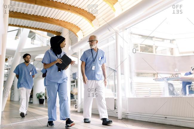 Confident female nurse talking to senior colleague in hospital corridor