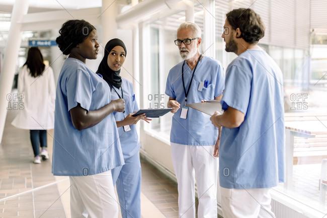 Confident male and female nurses talking in hospital corridor