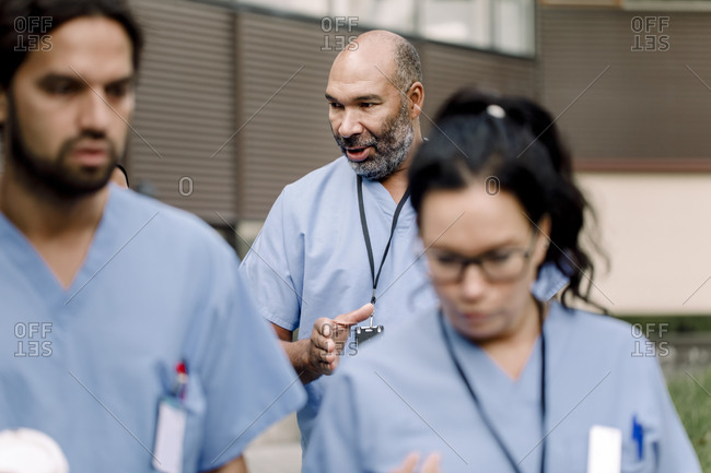 Mature nurse gesturing while talking to colleague outside hospital