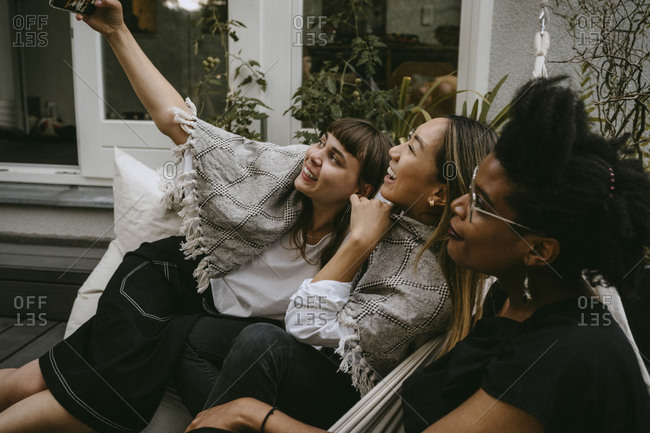 Smiling woman taking selfie with friends through mobile phone during social gathering